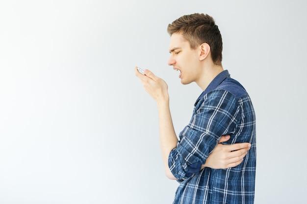 Młody człowiek krzyczy do telefonu. obsługuje opowiadać przez telefon na jasnopopielatym tle