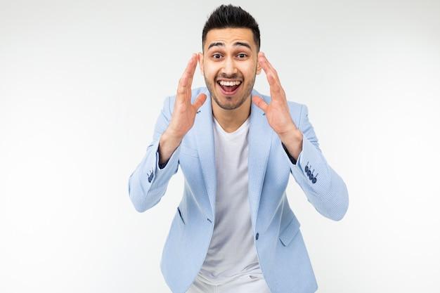 Młody człowiek krzyczy wiadomość na bielu z kopii przestrzenią w niebieskiej kurtce