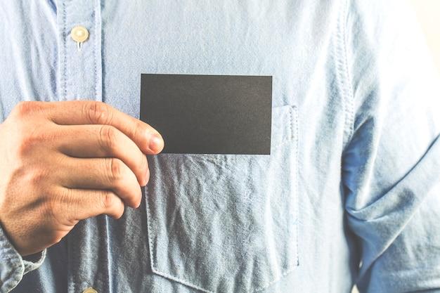 Młody człowiek, który wydobywa pustą wizytówkę z kieszeni koszuli
