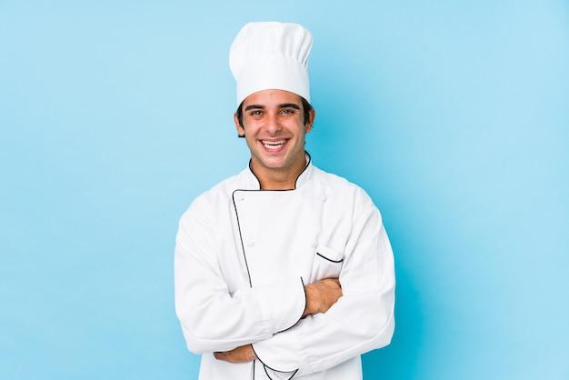 Młody człowiek kucharz na białym tle śmiejąc się i zabawy.