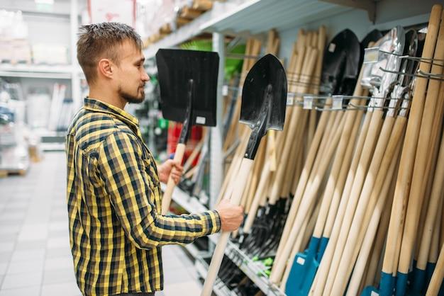 Młody człowiek kupuje łopatę w supermarkecie. mężczyzna klient na zakupy w hipermarkecie, dział narzędzi