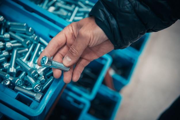 Młody człowiek kupuje narzędzie ręczne w sklepie sprzętu