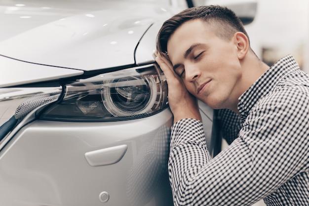 Młody człowiek kupuje nowy samochód przy przedstawicielstwem handlowym