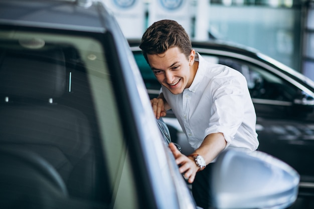 Młody człowiek kupuje samochód w sala wystawowej