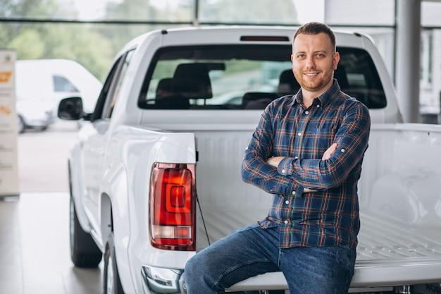 Młody człowiek kupuje samochód w samochodowej sala wystawowej