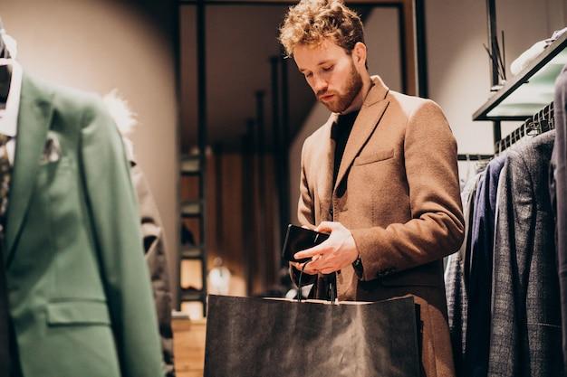 Młody człowiek kupuje ubrania i płaci gotówką przy sklepem