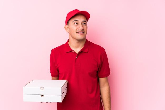 Młody człowiek łaciński dostawy pizzy na białym tle marzy o osiągnięciu celów i zamierzeń