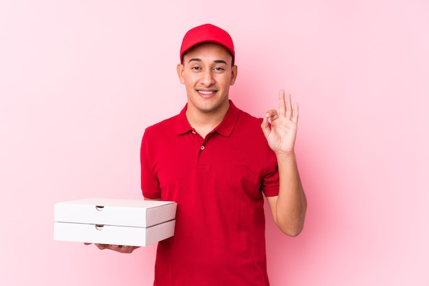 Młody człowiek łaciński dostawy pizzy na białym tle wesoły i pewny siebie, pokazując ok gest.