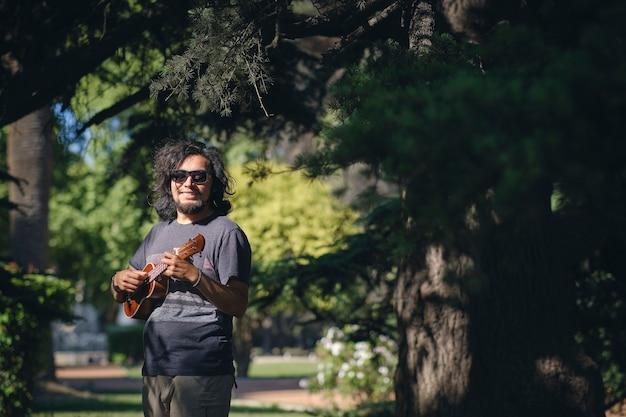 Młody człowiek łaciński mapuche z okularami przeciwsłonecznymi grający na ukulele w odkrytym parku