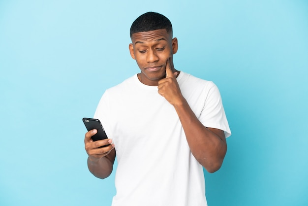 Młody człowiek łaciński na białym tle na niebieskiej ścianie za pomocą telefonu komórkowego i myślenia