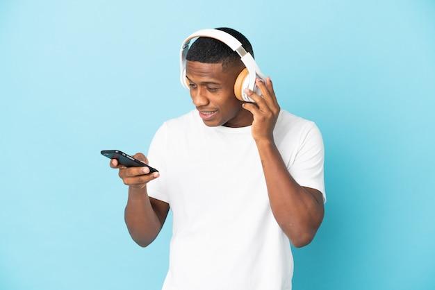 Młody człowiek łaciński na białym tle słuchanie muzyki z telefonem komórkowym i śpiewem