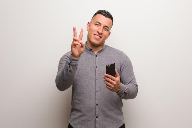 Młody człowiek łacińskiej posiadający telefon pokazujący numer dwa
