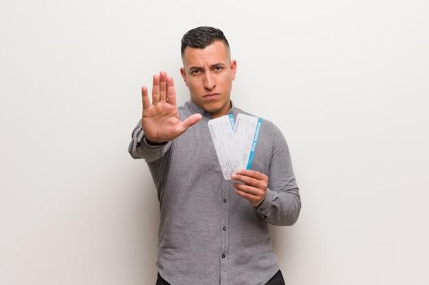 Młody człowiek łacińskiej posiadających bilety lotnicze, kładąc rękę z przodu