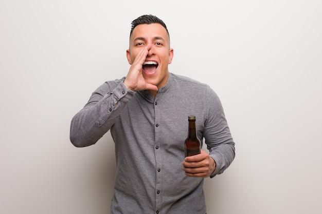 Młody człowiek łacińskiej trzyma piwo krzyczy coś szczęśliwego do przodu