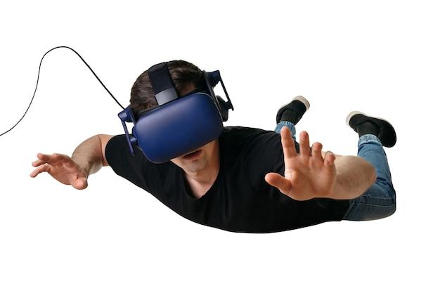 Młody człowiek latający w przestrzeni zerowej grawitacji i doświadczający wirtualnej rzeczywistości w goglach 3d, na białym tle