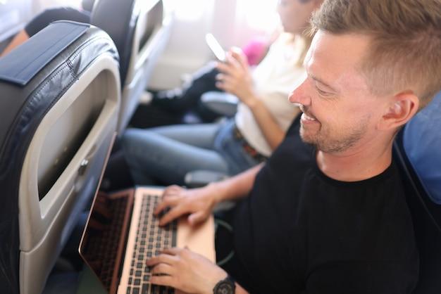 Młody człowiek latający w samolocie i piszący na klawiaturze laptopa