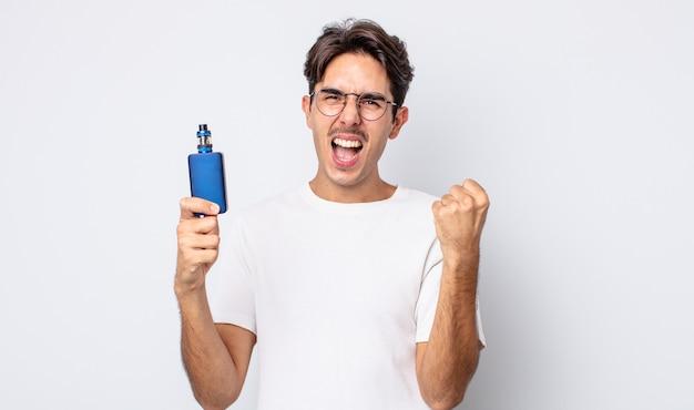 Młody człowiek latynoski czuje się w szoku, śmieje się i świętuje sukces. koncepcja parownika dymu