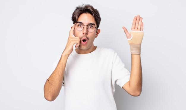 Młody człowiek latynoski patrząc zaskoczony, realizując nową myśl, pomysł lub koncepcję. koncepcja bandaża ręcznego