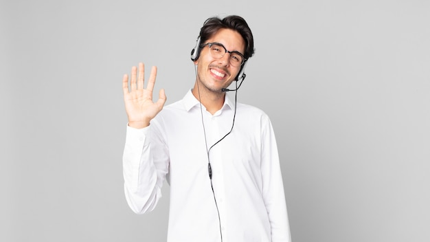 Młody człowiek latynoski uśmiechający się radośnie, machający ręką, witający i witający cię. koncepcja telemarketera