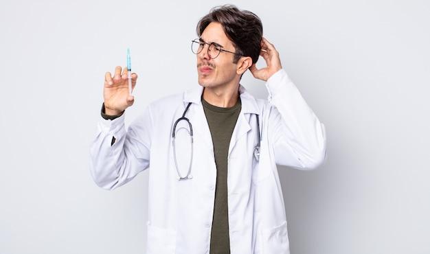 Młody człowiek latynoski uśmiechający się szczęśliwie i marzący lub wątpiący. koncepcja strzykawki lekarza