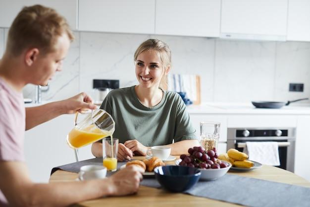 Młody człowiek leje świeży sok pomarańczowy w szklance swojej żony na śniadanie