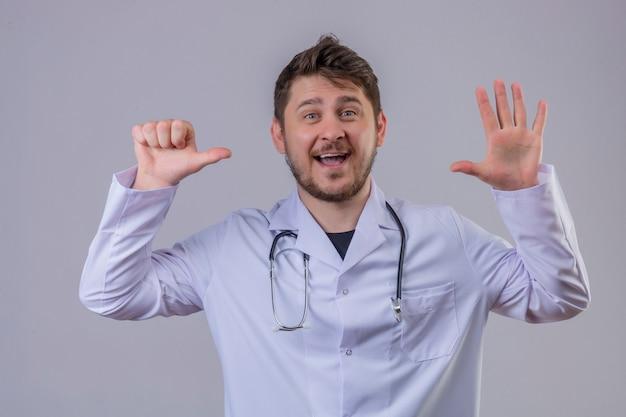 Młody człowiek lekarz ubrany w biały fartuch i stetoskop pokazujący numer sześć z uśmiechem dłoni i palców