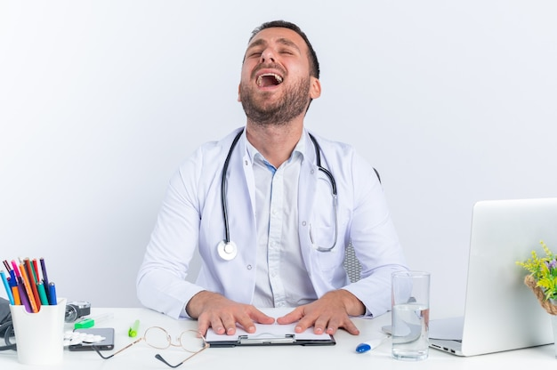 Młody człowiek lekarz w białym fartuchu i ze stetoskopem zdenerwowany płacz mocno jest sfrustrowany, siedząc przy stole z laptopem nad białą ścianą