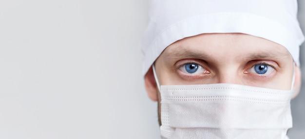 Młody człowiek lekarz w czapce i masce
