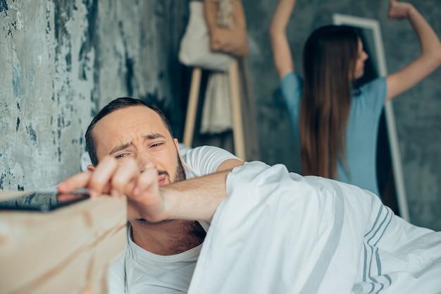 Młody człowiek leżąc w łóżku i dotykając swojego smartfona. młoda kobieta rozciągająca się na tle
