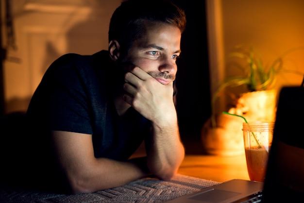 Młody człowiek leżący na podłodze z laptopem, czytając ciekawe artykuły