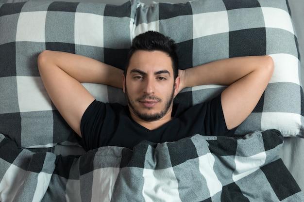 Młody człowiek leżący w łóżku