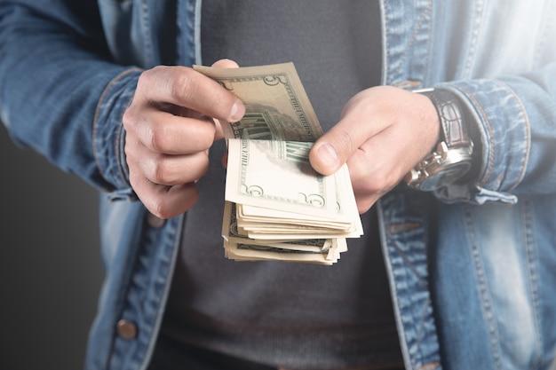 Młody człowiek liczy pieniądze obliczanie pieniędzy koncepcja biznesowa