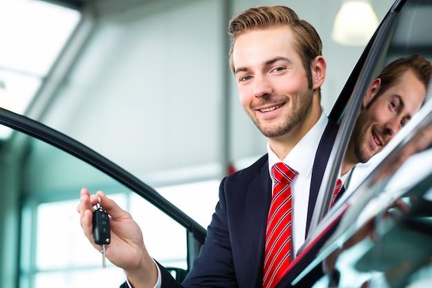Młody człowiek lub dealer samochodowy w salonie samochodowym