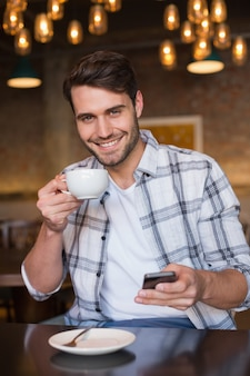 Młody człowiek ma filiżankę kawy