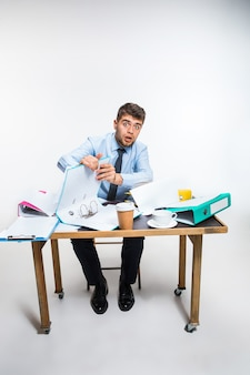 Młody człowiek ma kompletny bałagan w miejscu pracy, nie potrafi uporządkować swojej przestrzeni i znaleźć ważnych dokumentów. pojęcie kłopotów pracownika biurowego, biznesu, reklamy, codziennych problemów.