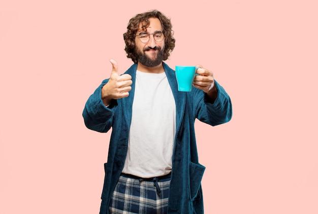 Młody człowiek ma na sobie szlafrok nocy garnitur o kawy