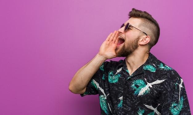 Młody człowiek ma na sobie wygląd wakacje krzycząc i trzymając palm blisko otwartych ust.