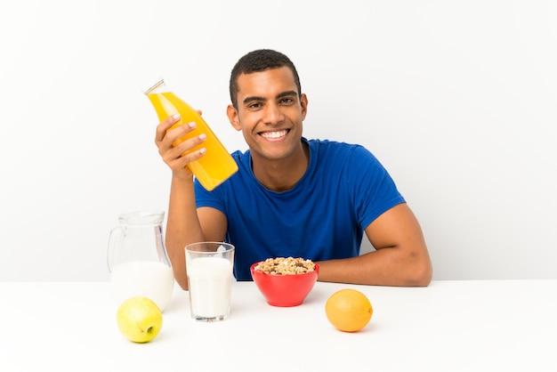 Młody człowiek ma śniadanie w stole