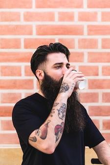 Młody człowiek ma tatuaż na jego ręce pije kawę przeciw ściana z cegieł
