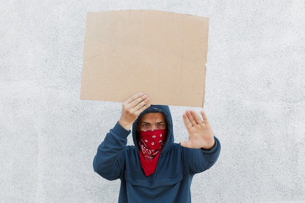 Młody człowiek macha ręcznie kartonowe afisz z miejscem na napis