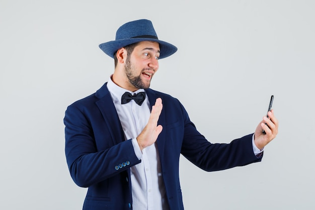 Młody człowiek macha ręką podczas rozmowy wideo w garniturze, kapeluszu i optymistycznie wyglądający widok z przodu.