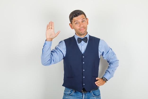 Młody człowiek macha ręką w geście cześć w garniturze, dżinsach i patrząc wesoło