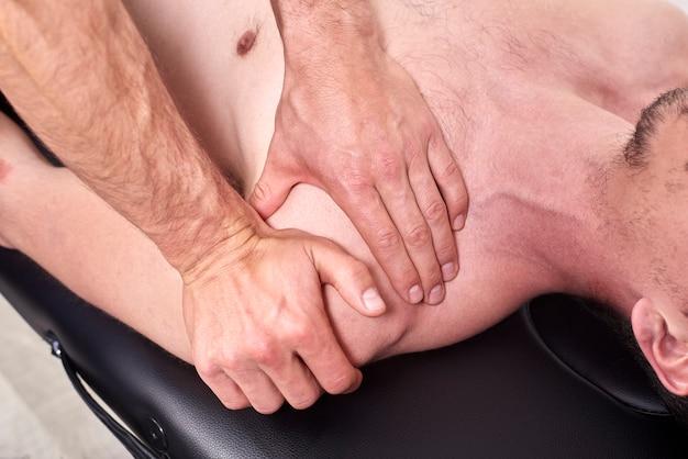 Młody człowiek mający chiropraktyka regulacji ramion.