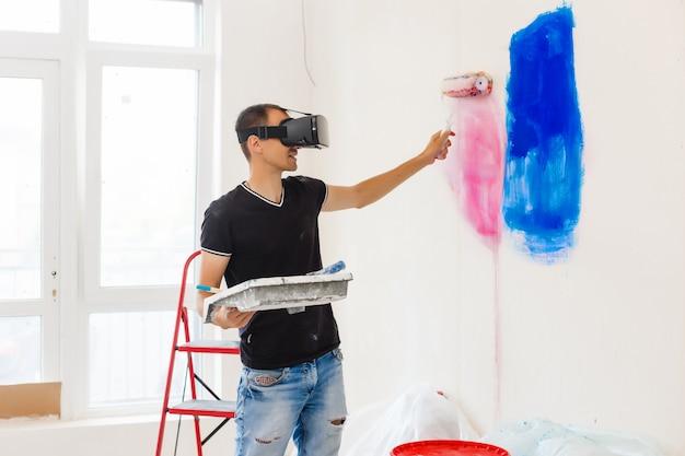 Młody człowiek malujący ścianę z wirtualnymi okularami