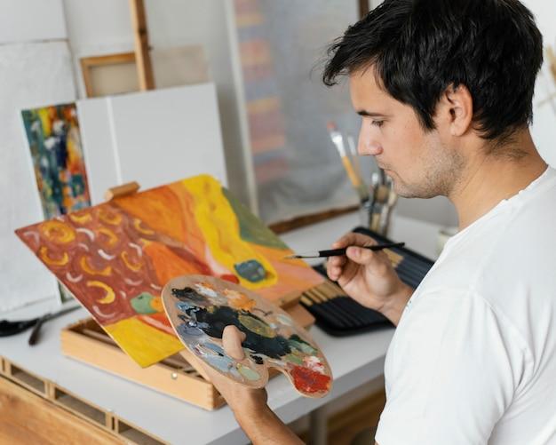 Młody człowiek maluje akrylem
