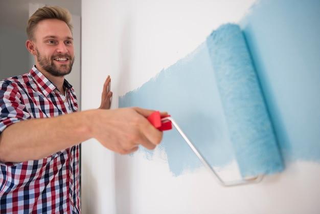 Młody człowiek maluje niebieską ścianę