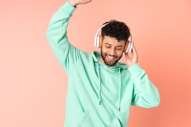 Młody człowiek maroka na białym tle na różowej ścianie, słuchanie muzyki i taniec