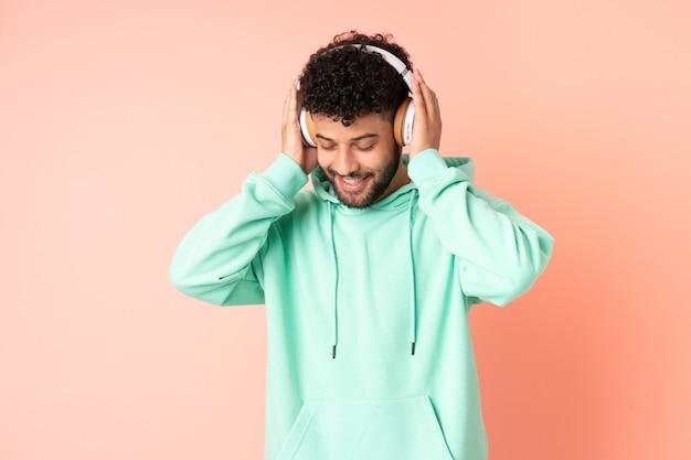 Młody człowiek maroka na białym tle na różowym tle słuchania muzyki