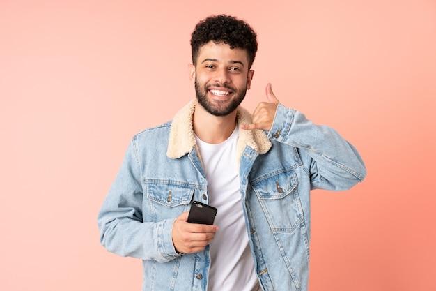 Młody człowiek maroka za pomocą telefonu komórkowego na białym tle na różowej ścianie, dzięki czemu telefon gest. oddzwoń do mnie znak
