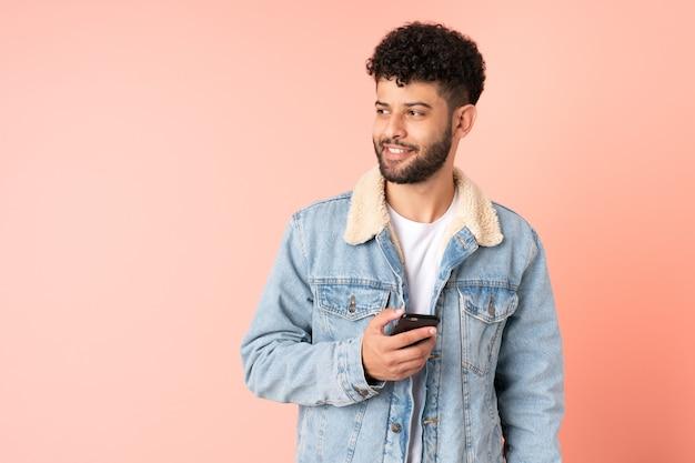 Młody człowiek maroka za pomocą telefonu komórkowego na białym tle na różowym tle, patrząc z boku i uśmiechnięty